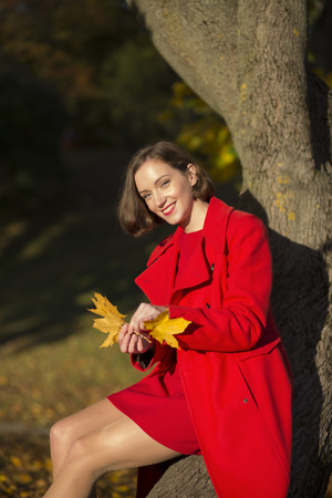 goldy: Young woman at autumn park and goldy leaves
