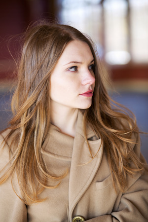 suprise: Young woman in beige coat with suprise look Stock Photo