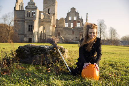 single story: Witch with pale skin with pumpkin is smiling
