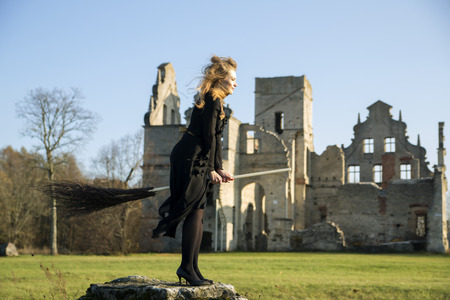 single story: Witch with pale skin with broom on stone Stock Photo