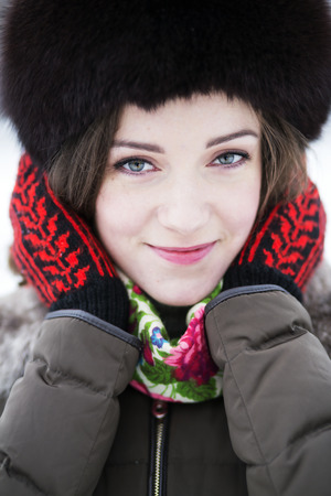 zoomed in: Zoomed portrait of a female in colored mittens Stock Photo