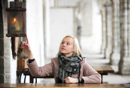 self discovery: Blonde with a short hairstyle sits and looking at the lantern Stock Photo