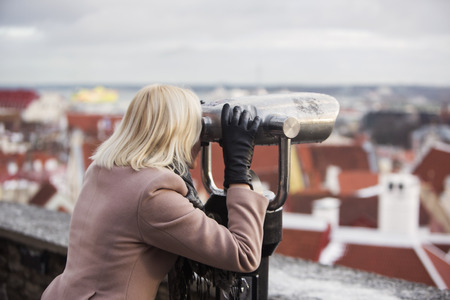 self discovery: Blonde woman takes a looks on the city through binoculars