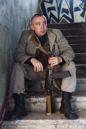 millitary: The skinhead hitman sitting on the stairs