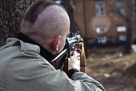 millitary: Shaved skinhead is aiming at the window