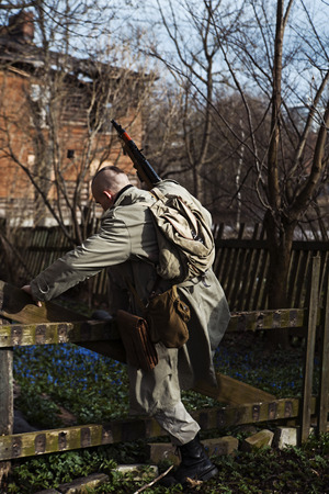 millitary: A shaved hunter stepps over the fence