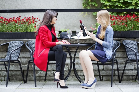 feel affection: Friends chatting and drinking wine in cafe Stock Photo