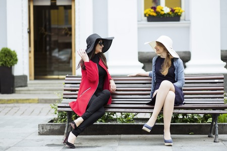 couple talking: Elegant female couple chatting in the square