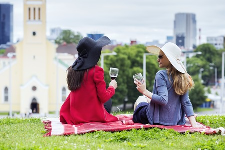 feel affection: Two female friends drinking together red wine