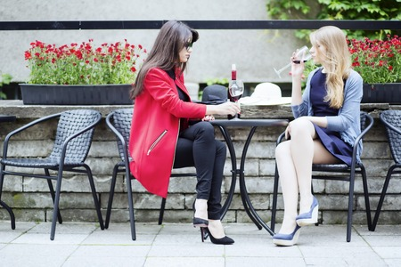 feel affection: Two beautiful women share red wine together
