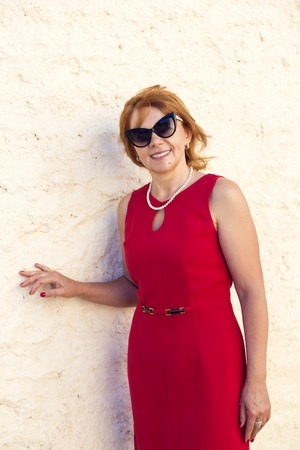 broadly: Mature woman in red dress smiles broadly Stock Photo