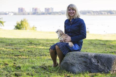 dog rock: Woman sitting on rock holds little dog