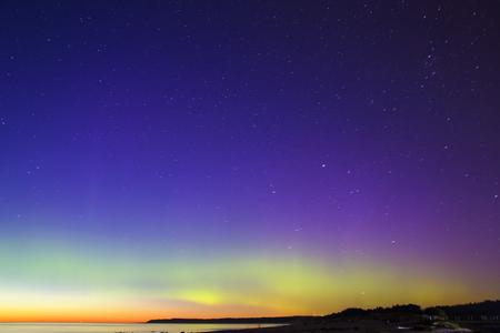 aurora: Warm Aurora Borealis above the Northern Sea Stock Photo