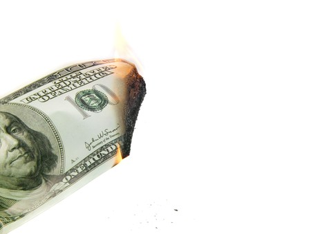 blazes:  dollar banknote blazes aflame on white background