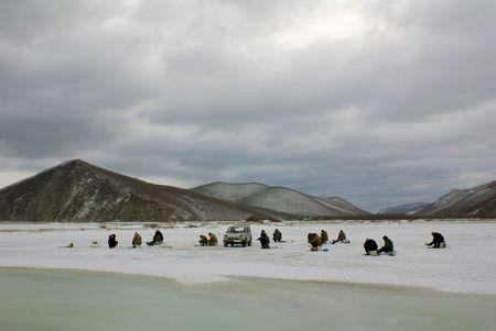 fishermen go fishing in winter on ice photo