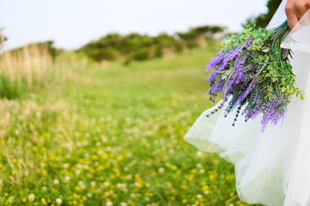 Woman in white dress holding purple bouquet on a cliff full of yellow blossoms in Jeju Island, Korea.