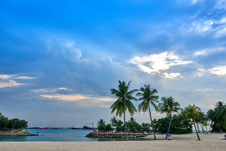 The view of Siloso Beach with palm trees, ships on the ocean, and magnificent clouds in the sky.