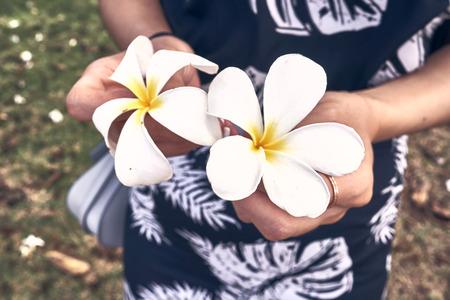 A woman in hawaiian dress holding Plumeria Kauai, one of Hawaii's popular tropical flowers.
