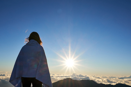 A woman looking at the horizon at the peaks of Haleakala mountain during sun rise.