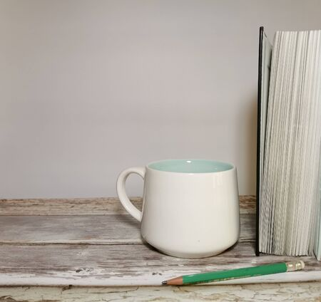 Book, pencil and white mug on a wooden table. White background. Space for your text. Image with selective focus and with toning. 版權商用圖片
