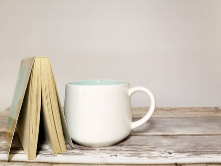 Book and white mug on a wooden table. White background. Space for your text. Image with selective focus and with toning.