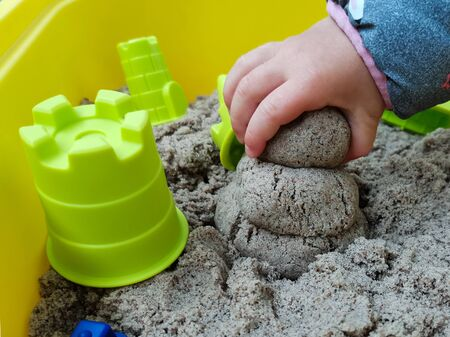 The child makes of a sandyman from kinetic sand. Pictured is a child's hand holding sand and plastic kinetic sand toys. Kinetic sand is a natural color. Image with selective focus. Stock fotó
