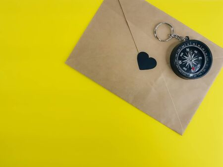 Craft envelope with a heart and a hand compass on a yellow background. The concept of love for romantic travels and letters from other countries. Blank for your text