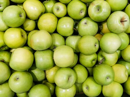 Solid background of green apples in a crate. Many organic Granny Smith apples. Healthy and affordable fruits in the supermarket, source of vitamin C. Pattern for design. View from above.