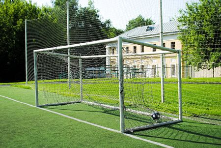 A ball in a soccer goal on an amateur soccer field on a sunny summer day. Gates with a torn and dirty net. Sports group games on a professional and amateur level. Summer outdoor sports.