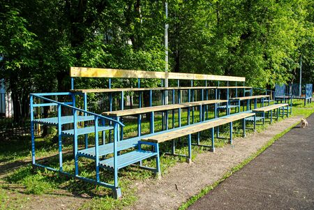 Empty spectator stand on an amateur soccer field. Wooden grandstand at the school stadium. Sports group games on an amateur level. Summer outdoor sports.
