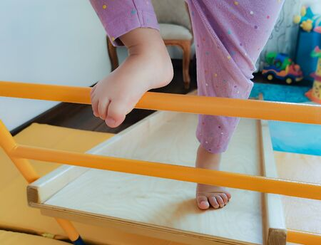 Legs of a todler climbing a frame a staircase of a home sports complex. Sports games with children in the apartment. Early development, children's physical education, exercise and gymnastics at home