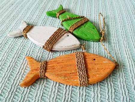 Three wooden decorative fish of red, green and white, tied with twine. Interior items in country style.Creating comfort through small details in the design.Image with selective focus in the foreground