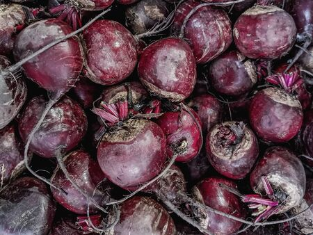 Unpeeled raw beets on a market counter. Background from the same vegetables. Farm root crops. Healthy vegetarian food. Beetroot reduces blood pressure, the risk of diabetes and improves digestion. Stock fotó