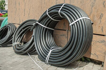 A rolled up black industrial rubber hose tied with rope on the street. Products for irrigation systems, work in suburban estates and agriculture. Tools used in plumbing work. Archivio Fotografico