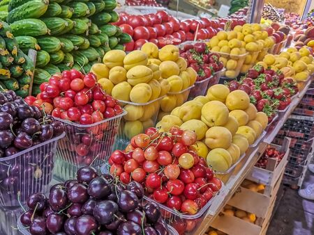 Dark cherries, cherries, apricots, strawberries and vegetables laid out on the counter of the farmers ' market. Healthy organic products from the farm. Seasonal berries, vegetables and fruits. Standard-Bild