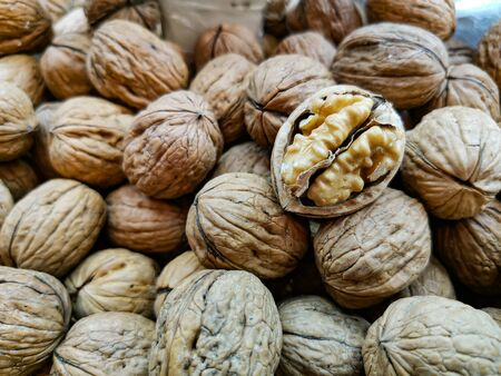 Closeup of shelled peeled walnut on a farmer's market counter. Background of nuts. Healthy nutrition and vitamins.