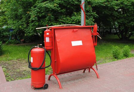 The fire set installed at a gas station. It consists of fire extinguishers, a box sand, a shovel for elimination of fire. A gas station is a place where security measures must be at the highest level Standard-Bild - 150183451