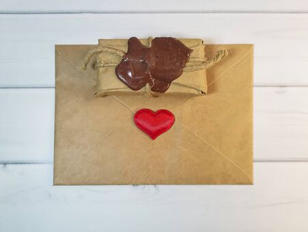 Delivery box tied with twine with a wax seal with an envelope from craft paper with a red heart. Concept: free delivery, gifts, vintage souvenirs, Love message, letter of recognition.