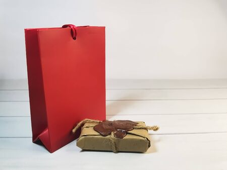 A red gift bag and a small package with a wax seal, tied with twine on wooden boards. Romantic gift, declaration of love, a symbol of love. Place for text or logo.