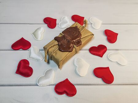 A small parcel with a wax seal tied with twine and many white and red hearts on wooden boards. Romantic gift, declaration of love, a symbol of love. Фото со стока