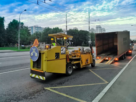 Road marking machine on a wide avenue of the city. Urban road safety.