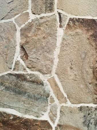 Close up uneven natural shape stone shades of brown and gray - wall materials in classic building patterns. Ancient castle. Part of a stone wall, for background or texture