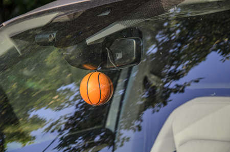 Keychain pendant in the form of a small basketball on the rearview mirror of a car. Photo through a dusty windshield with trees reflecting. Sports attributes. Car decoration