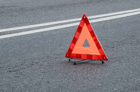 Red warning triangle on the carriageway with a double dividing strip. Traffic rules, traffic accidents, road safety. Zdjęcie Seryjne