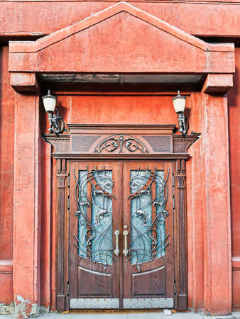 Dark red stone building facade with wooden door and lanterns. Door with Baroque forged metal grating formed in a pattern of leaves