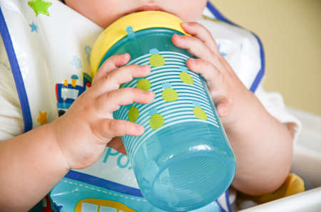 One-year-old child holds a spill-proof drinking bowl with two hands. Baby hands close-up. Infant nutrition. Stock Photo