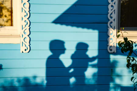 Shadowy silhouettes of mother and child on the blue facade of country house with white carved trims on summer evening. The mother supports and ensures the safety of child. The concept parental care