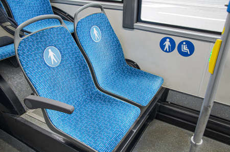 Blue fabric seats in the bus for elderly, people with disabilities and passengers with children. Special seats in public transport for certain categories of passengers.