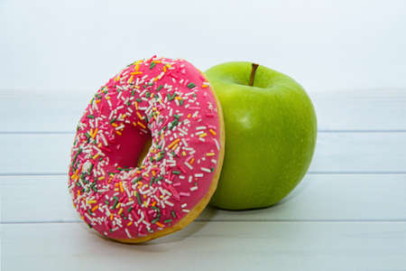 Green apple and donut with strawberry icing and multicolored sprinkles on light wooden table. Concept of proper nutrition, comparison of harmful and healthy food. Dietary choices, healthy lifestyle Stock Photo