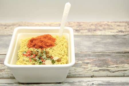 Instant dryed noodles with dry vegetables and spices with red pepper in disposable container with plastic fork. Traditional cheap Asian food. Fast food, raw noodles. Space for text
